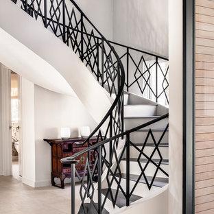 Modelo de escalera curva, actual, grande, con escalones con baldosas y contrahuellas de madera pintada