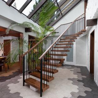 バンクーバーの中くらいの木のミッドセンチュリースタイルのおしゃれな階段 (混合材の手すり) の写真