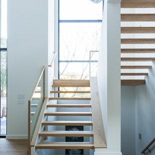 Diseño de escalera suspendida, actual, sin contrahuella, con escalones de madera y barandilla de vidrio