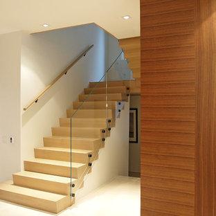 Imagen de escalera en U, minimalista, de tamaño medio, con escalones de madera, contrahuellas de madera y barandilla de vidrio