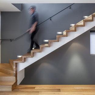 Ejemplo de escalera en L, actual, con escalones de madera y contrahuellas de madera