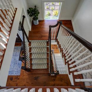 Diseño de escalera en U, de estilo de casa de campo, extra grande, con escalones de madera, contrahuellas de madera pintada y barandilla de madera