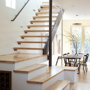 """Foto di una grande scala a """"L"""" moderna con pedata in legno, alzata in legno e parapetto in legno"""