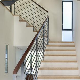 Cette photo montre un escalier tendance en L avec des marches en bois, des contremarches en bois peint et un garde-corps en métal.