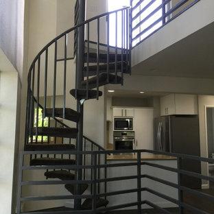 Esempio di una scala a chiocciola minimal di medie dimensioni con pedata acrillica e parapetto in metallo