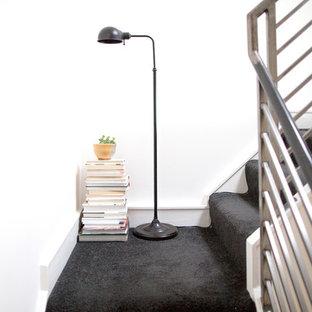 Modelo de escalera en L, nórdica, de tamaño medio, con escalones enmoquetados, contrahuellas enmoquetadas y barandilla de metal