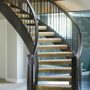 Diseño de escalera curva, de estilo americano, sin contrahuella, con escalones enmoquetados y barandilla de madera