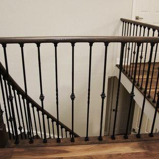 Diseño de escalera curva, clásica renovada, grande, con escalones de madera, contrahuellas de madera pintada y barandilla de varios materiales