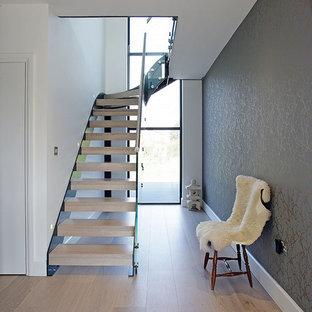 Imagen de escalera en L, moderna, de tamaño medio, con escalones de madera, contrahuellas de madera y barandilla de vidrio