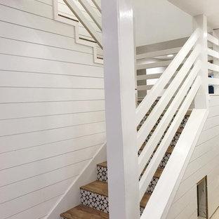 Imagen de escalera curva, campestre, de tamaño medio, con escalones de madera pintada, contrahuellas de madera y barandilla de madera