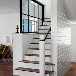 Foto på en lantlig trappa i trä, med sättsteg i målat trä