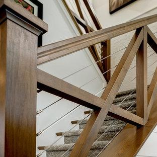 Ejemplo de escalera en U, de estilo de casa de campo, de tamaño medio, con escalones enmoquetados, contrahuellas enmoquetadas y barandilla de madera