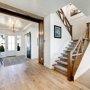 Inspiration for a mid-sized country carpeted u-shaped staircase in Boise with carpet risers and wood railing.