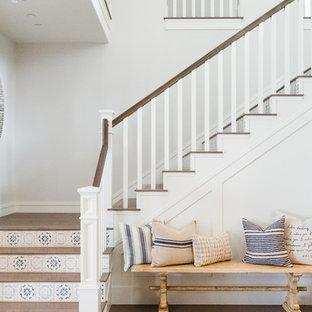 """Immagine di una scala a """"L"""" stile marino con pedata in legno, alzata piastrellata e parapetto in legno"""