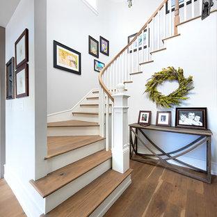 Imagen de escalera curva, campestre, de tamaño medio, con escalones de madera, contrahuellas de madera pintada y barandilla de madera