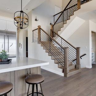 На фото: п-образные лестницы в стиле кантри с деревянными ступенями, деревянными подступенками и перилами из смешанных материалов