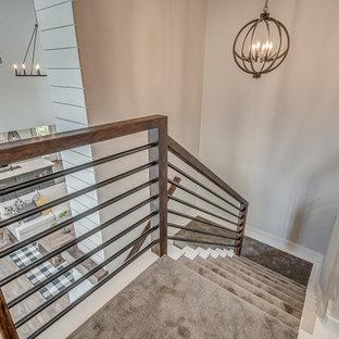 Cette photo montre un grand escalier nature en U avec des marches en moquette, des contremarches en moquette, un garde-corps en métal et du lambris de bois.