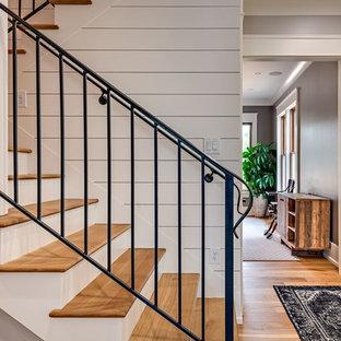 Diseño de escalera en U, de estilo de casa de campo, de tamaño medio, con escalones de madera, contrahuellas de madera pintada y barandilla de metal