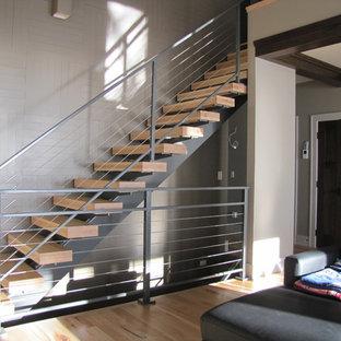 На фото: прямая лестница среднего размера в стиле модернизм с деревянными ступенями и перилами из тросов без подступенок с