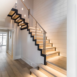 Esempio di una grande scala sospesa minimalista con pedata in legno, alzata in metallo e parapetto in metallo