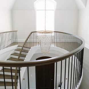 Modelo de escalera curva, clásica renovada, grande, con escalones de madera pintada, contrahuellas de madera y barandilla de varios materiales