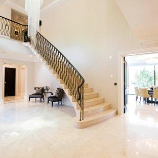 Ejemplo de escalera curva, minimalista, grande, con escalones de travertino, contrahuellas de travertino y barandilla de metal