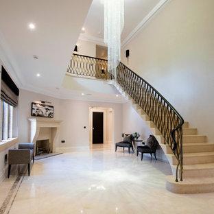Cette image montre un grand escalier courbe minimaliste avec des marches en travertin, des contremarches en travertin et un garde-corps en métal.