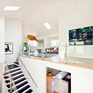 Imagen de escalera contemporánea, grande, con barandilla de vidrio, escalones de madera y contrahuellas de madera pintada