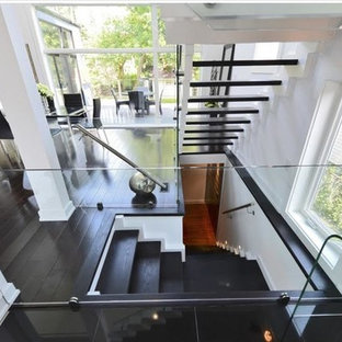 Example of a large minimalist painted l-shaped wood railing staircase design in Toronto with painted risers