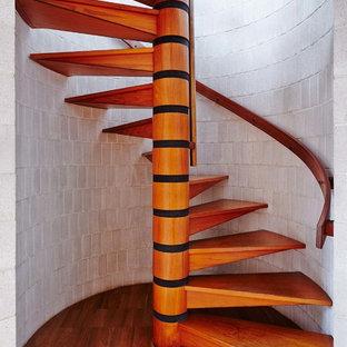Bild på en stor funkis spiraltrappa i trä, med öppna sättsteg