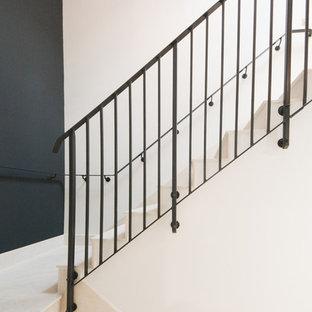 Diseño de escalera en U, minimalista, grande, con escalones de piedra caliza, contrahuellas de piedra caliza y barandilla de metal