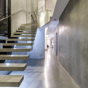 Foto de escalera suspendida, minimalista, de tamaño medio, sin contrahuella, con escalones de hormigón y barandilla de metal