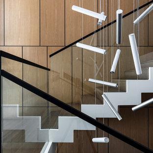 Modelo de escalera en L, minimalista, de tamaño medio, con escalones de travertino, contrahuellas de madera y barandilla de vidrio