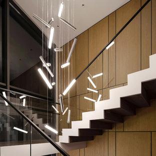 """Immagine di una scala a """"L"""" minimalista di medie dimensioni con pedata in travertino, alzata in legno e parapetto in vetro"""