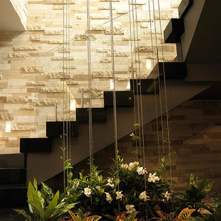 Diseño de escalera suspendida, minimalista, de tamaño medio, con escalones de metal, contrahuellas de madera pintada y barandilla de vidrio