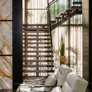 Trendy wooden open and glass railing staircase photo in Miami
