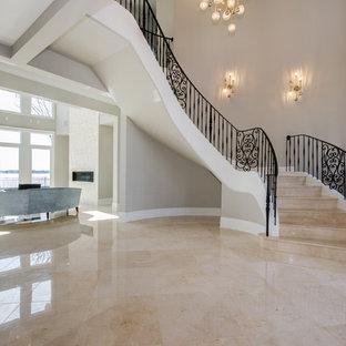 Foto på en stor funkis svängd trappa i marmor, med sättsteg i marmor och räcke i metall