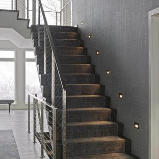 Ejemplo de escalera en U, actual, de tamaño medio, con barandilla de metal, escalones de madera y contrahuellas de madera