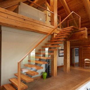 Esempio di una scala sospesa moderna con pedata in legno, alzata in legno e parapetto in vetro