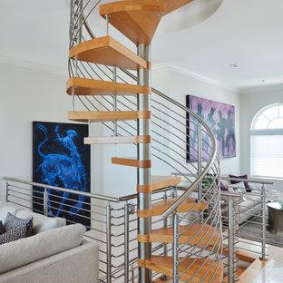 Esempio di una grande scala a chiocciola minimal con pedata in legno, nessuna alzata e parapetto in metallo