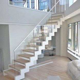 Immagine di una grande scala a rampa dritta moderna con pedata in legno, nessuna alzata e parapetto in vetro