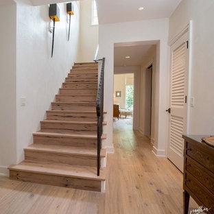 На фото: большая прямая лестница в стиле кантри с деревянными ступенями и металлическими подступенками с