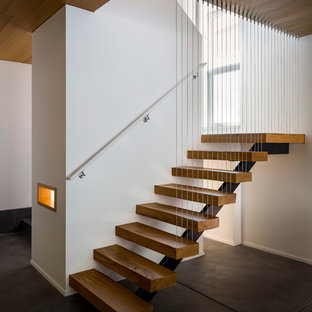 Photo of a medium sized modern wood u-shaped staircase in San Francisco with open risers.