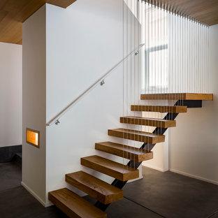 Imagen de escalera en U, moderna, de tamaño medio, sin contrahuella, con escalones de madera