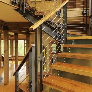 Bild på en funkis trappa i trä, med sättsteg i metall och kabelräcke