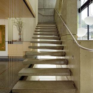 Ejemplo de escalera suspendida, moderna, sin contrahuella, con escalones de hormigón y barandilla de metal