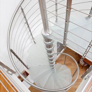 Ispirazione per una scala a chiocciola minimalista con pedata in vetro e nessuna alzata
