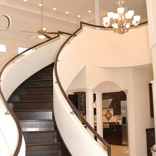 Example of a large transitional painted curved staircase design in Chicago with wooden risers