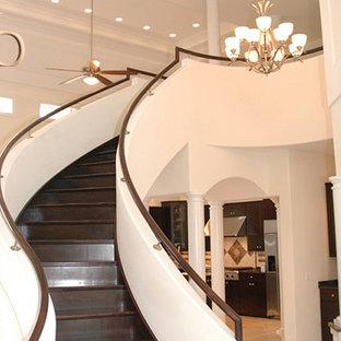 Ejemplo de escalera curva, tradicional renovada, grande, con escalones de madera pintada y contrahuellas de madera