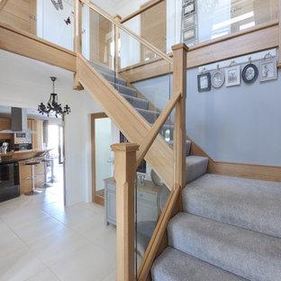 Foto de escalera en L, actual, de tamaño medio, con escalones enmoquetados, contrahuellas de madera y barandilla de madera